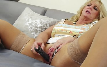 A granny plays with her old pussy with a dildo close up